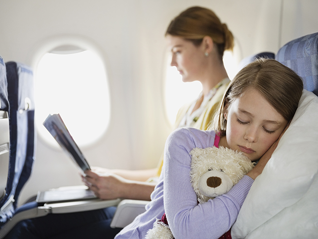 A young girl naps with her teddy bear in the middle seat.